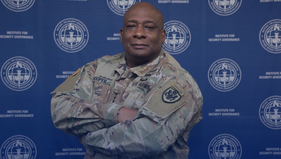 photo of LTG Charles Hooper in front of a blue screen with white ISG logos