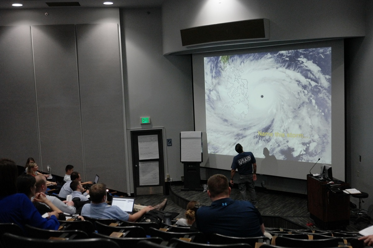 Participants watching projector screen with hurricane image on it