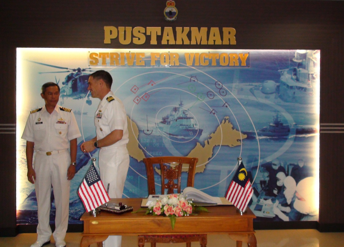Two officers in white uniforms in front of a collage image of naval ships